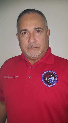 Man with red, short-sleeve, collar shirt. The left of the man's shirt reads, H. Velazquez, ICT. The right of the man's shirt has a blue, red and black seal that reads, VA Caribbean Healthcare System and San Juan Puerto Rico.