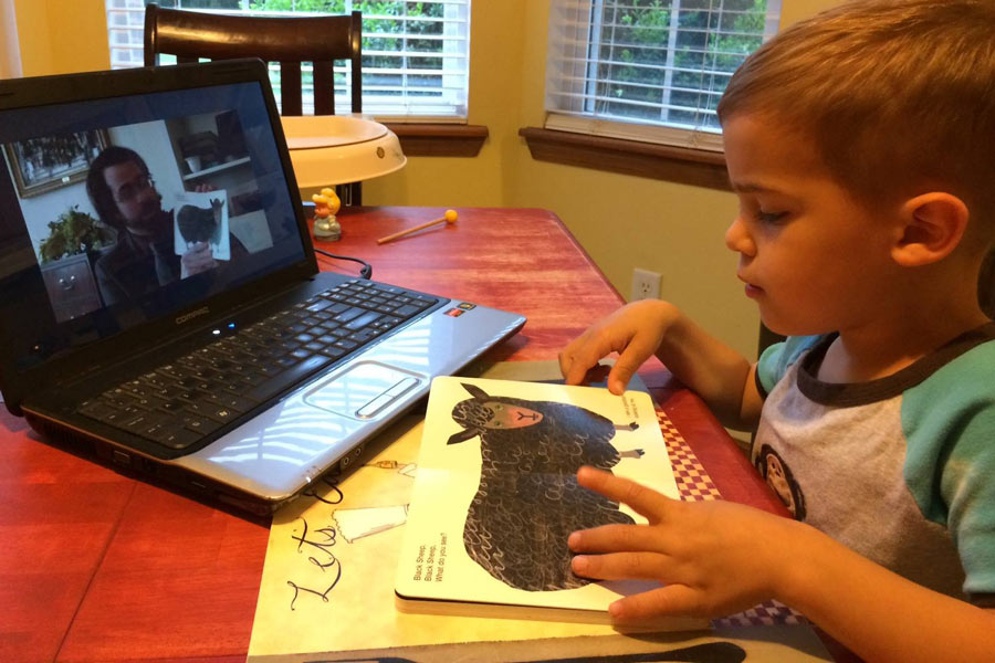 A child reading a book is guided through the book by their parent, a service member, via videophone.