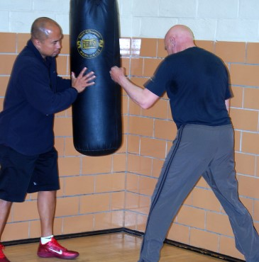A Veteran is holding a heavy bag still while another Veeteran practices boxing punches