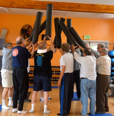 A group of Veterans hold up their large foam rollers after completing a strength and wellness class.