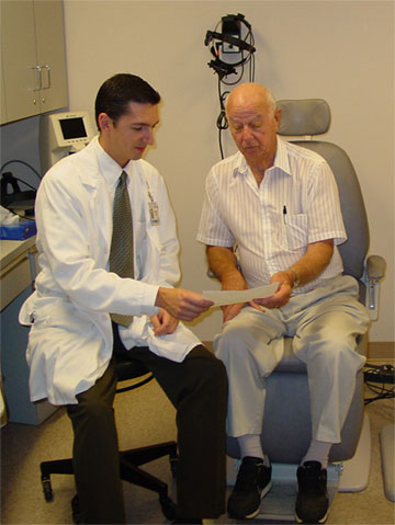 Photo of a doctor reviewing an educational information sheet with a patient.