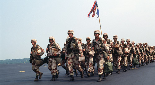 Soldiers in desert camo uniforms marching