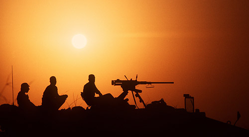 Silhouette of three soldiers in the sunset