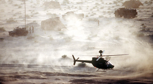 Aerial photo of a helicopter flying over the desert