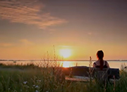 Woman sitting on bench looking at sunset