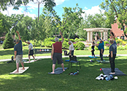 Veterans practice yoga poses outside in a garden