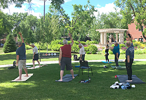 Veterans practice yoga poses outside in a garden