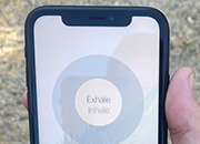 Image of a veteran using mobile phone app for mindful breathing