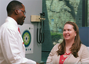 Doctor discusses treatment with woman patient sitting in an exam room with a Whole Health poster on the wall.