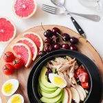 Bowl of cherries, chicken, eggs, avocado, tomatoes, and grapefruits.