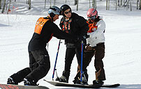 Photograph of a disabled veteran being readied on a snowboard