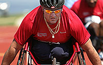Photograph of diasabled veteran racing in a wheelchair