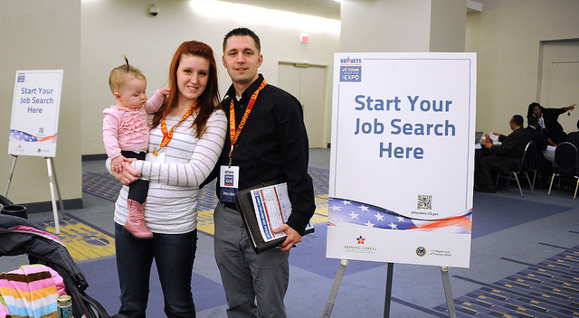 Veterans (husband and wife) holding baby at hiring fair