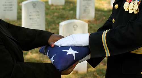 Image of a folder American Flag being handed over to a family member at a VA National Cemetery