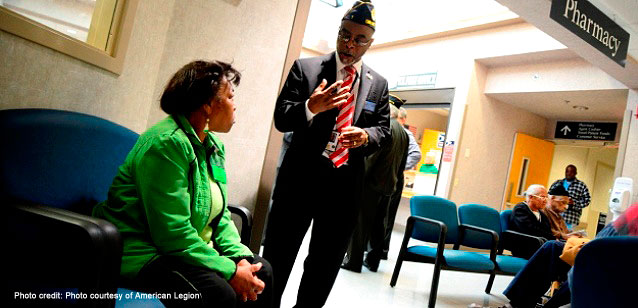 An American Legion official visits with a Veteran