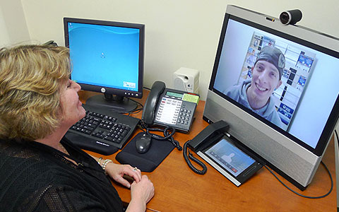 Woman and man speaking to each other via video over the Internet