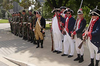 Current day soldiers along with reenactors dressed in revolutionary war uniforms