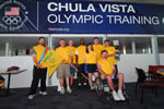 Veteran athletes and instructors pose for a picture in front of the Chula Vista Olympic Training Center sign.