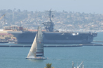 A sailboat passes by a United States Navy aircraft carrier in San Diego Bay.