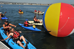 People in kayaks paddling around a large multi-colored floating ball.