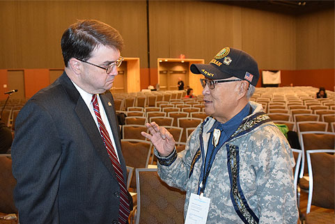 Image of Secretary Wilkie speaking with Alfie Alvarado, State Director